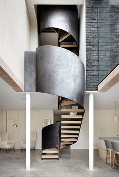 Steel-wrapped staircase winds through Cousins & Cousins' laminated timber and glass extension in Hackney