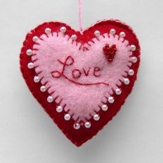 A handmade heart created with two colors of felt, and blanket-stitched by hand with faux-pearl and bead details. #heart #love