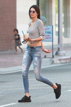 Kendall Jenner wears a striped crop t-shirt, distressed skinny jeans, Yeezy Boost black sneakers, and round sunglasses