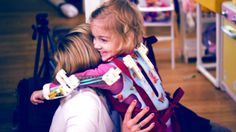 A little girl with 3D printed arm braces smiles and hugs her mom