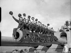 Sailors of the South African Royal Naval Volunteer Reserve sitting on one of the 16 inch gun barrels of HMS Nelson during World War II.