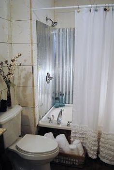 Corrugated tin shower surround teamed with ruffled curtains....a terrific country bathroom look