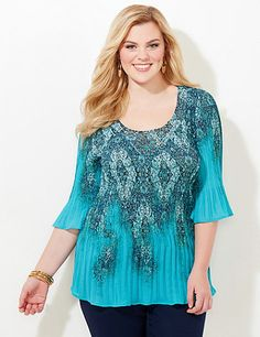 Feel the vibe with this bright and beautiful top in a stunning print. The unique pleats gracefully release at the hem for a flowing finish. Studded scoop neckline. Three-quarter sleeves. Catherines tops are designed for the plus size woman to guarantee a flattering fit. catherines.com