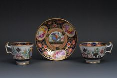Lot 103 - sold for £650 A Swansea Porcelain London Shape Teacup, Coffee Cup And Saucer, Painted With Oval Cartouches With Colourful Summer Flowers On A Pink Ground, The Cobalt Blue Ground With Orange Flowers And Gilt Scrolls, Angular Handles, Marked Swansea No.210, C.1813-20