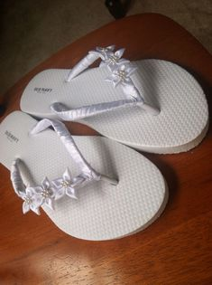 DIY Wedding flip flops great for getting ready and for dancing when the heels just won't do! Just hot glue thin ribbon on the V very slowly and be sure to make it tight then add flowers to make them bold and beautiful! (Bought flowers from Michaels and flip flops from old navy)