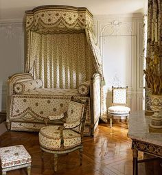 Ébéniste Georges Jacob made rustic-style furnishings for the Queen's Bedchamber, their painted frames carved with climbing ivy and accented with pinecone finials. Sold in 1793 during the imprisonment of Marie Antoinette, some of the objects shown were returned to Versailles in 1945.