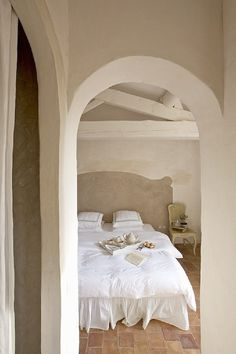 Simple white bed with terra cotta floors