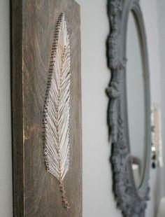timmer spijkers in een silhouet van een veer op een plank en verbind de spijkers met garen zoals op de voobeebeeldfoto