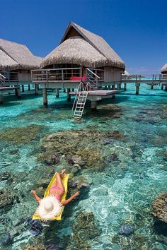 French Polynesia, Moorea, Woman sunbathing and relaxing floating on tropical water daydreaming