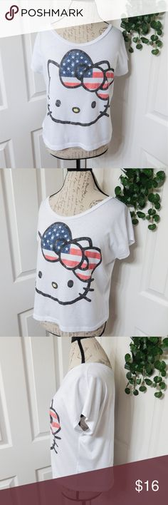"""Hello Kitty Crop Tee Size Small Hello Kitty is wearing a patriotic bow on this lightweight white cropped tee. Short sleeves & a dropped shoulder style, seems to run a little big in my opinion & could probably fit a size medium easily. In excellent condition!  50% cotton 50% polyester Chest approx 22"""" flat across front Length 21"""" from front shoulder seam Hello Kitty Tops Tees - Short Sleeve"""