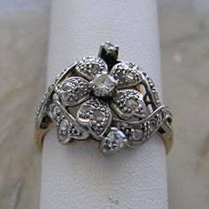 This Is A Truly Feminine And Pretty Antique Diamond Ring. The Silver Top 18K Yellow Gold Ring Sits Flat And Comfortable On The Finger. Designed With a Stylized Central Feminine Flower Design. The Ring...