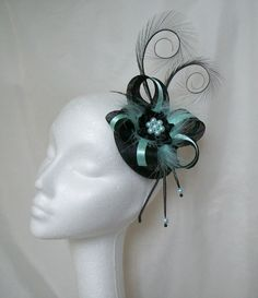 Black & Aqua Isabel Fascinator Mini Hat, Order Now from www.indigodaisyweddings.co.uk Specialising in stunning bespoke cocktail fascinators and formal hats in a wide range of colours, perfect for Royal Ascot and The Kentucky Derby. Plus all your wedding floral accessories including shoe clips, vintage flapper bands, feather and flower fascinators, feather fans, fairy wands, wrist corsages, wedding bouquets & buttonholes. Worldwide Delivery.