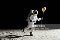 Stock Photo : An astronaut on the moon holding a heart shaped helium balloon