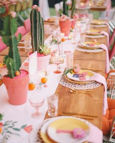 Other tables were set with pink potted cacti, citrus fruits, and floral runners. The pattern on the runners was hand painted by Peanut Press Creative…