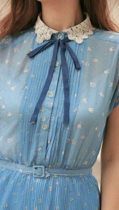 light blue, bowtie, lace collar, white flowers dress. Unsure of seller