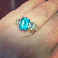 Bold blue topaz 14k ring This dramatic ring has a large emerald cut blue topaz in the middle and 3 smaller stones on each size, gradually decreasing in size and color hue. Set in 14k. Jewelry Rings