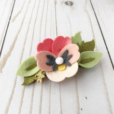 Felt flower Garden Pansy Meticulously handcrafted felt flower pansy hair piece adorned with leaves & gold glitter sprigs affixed to an alligator style clip or on a one size fits all stretch nylon headband. The perfect accent piece for baptisms, christenings, newborn sessions, flower girl,