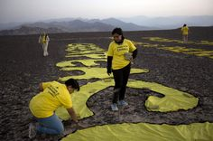 """Greenpeace activists arrange the letters delivering the message """"Time for Change: The Future is Renewable"""" next to the hummingbird geoglyph in Nazca, Peru, Monday, Dec. 8, 2014. Greenpeace activists from Brazil, Argentina, Chile, Spain, Germany, Italy and Austria displayed the message, which can be viewed from the sky, during the climate talks in Peru, to honor the Nazca people, whose ancient geoglyphs are one of the countries cultural landmarks. (AP Photo/Rodrigo Abd)"""