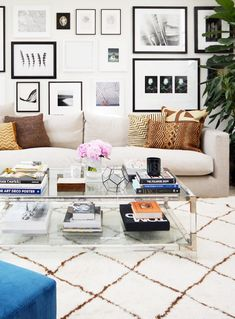 A feminine and sunny living space with gallery wall, glass coffee table, peonies, and animal print pillows