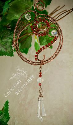 A Sun Catcher, it is copperwire shaped in circle with a spiral design, embellished with red beads, crystals and wire weaving create design