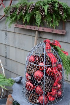 Love the old rake with greenery and pinecones.  The wire basket filled with red ornaments is the perfect touch.