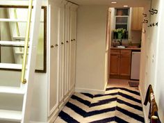 """Dear Genevieve """"Crash Pad to Pied-A-Terre"""" Those closets/shelves slide out! The ladder can be pushed flush with the wall for a little extra space when not in use. Love the mismatched hooks on the wall, graphic patterned carpet tiles, & bright, clean white!"""