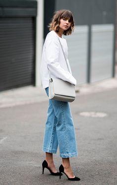 Street style looks com suéter, calça jeans e scarpin preto.