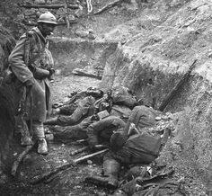 A French soldier smokes a cigarette, standing near the bodies of several soldiers, apparently Germans, near Souain, France, ca. 1915. (Bibli...