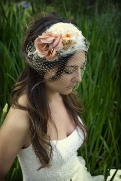 Feather pad headband decorated with peach vintage flowers and jewelry, bird cage veil.