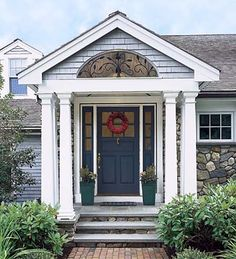 A gabled portico with six tapered columns and a fanciful interpretation of a fanlight—a half-round cut-out in the gable with wrought-iron grillwork—gives presence to the entry of this newly built seaside cottage but keeps the mood informal.    To add another level of detail, architect Thad Siemasko inlaid a band of purpleheart wood in the white-painted trim surrounding the door and sidelights. The fieldstone on the stair risers and the shingles and wood trim on the gable echo elements used…
