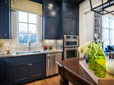 The dark staines wood island contrasts well against the blue shaker cabinets and black and white basket weave tile backsplash. Touches of green add warmth to the deep blues in this kitchen.