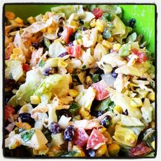 Healthy Chicken Taco salad. Black beans, corn, green peppers, tomatoes, cilantro, green onions, chicken, avocado & tortilla chips. All tossed together with a taco ranch dressing made with Greek yogurt.