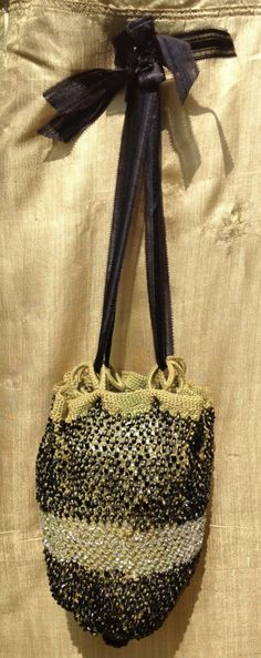 c1815 green wool knitted and beaded reticule. Black and clear glass beads knitted in, not just sewn on. 8 ribbon loops, original ribbon. Large black bead at base. 'Louisa Rousseau' embroidered around top.