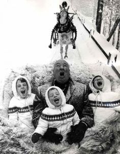 Alfred Hitchcock catching snowflakes during a sleigh ride with his grandchildren, 1960