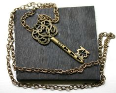 $24.00 A striking antique bronze key pendant hangs from a 24 inch antiqued brass chain. The key is 2.25 inches high and .75 inches at its widest.