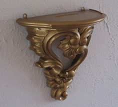 Swirly, sturdy, lovely gold shelf. Has two eye hooks on back for hanging. The top surface is designed with a slight ridge for propping up a decorative object. Sturdy -- weighs nearly one pound.  9 inches tall 8 1/2 inches wide 4 1/4 inches deep