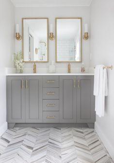 Brass fixtures in a bath with herringbone pattern floor