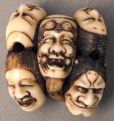Ivory netsuke depicting seven faces, five on one side and two on the other.