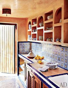 Beautiful Moroccan kitchen. Zellige tiling everywhere and Tadelakt in lieu of regular paint. Built in wall shelves instead of cupboards. As seen in AD magazine.