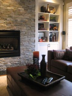 In this family room we up dated the fireplace and kept the existing open shelves. The original built-in had a rounded top, country style cupboard doors all dressed in oak. so we squared out the top, change the doors to match the adjacent kitchen cupboards and painted the whole unit white to coordinate with the window shutters. Not only did it make the room brighter, it also made the fireplace stand out. Top Country, Country Style, Round Ottoman, Window Shutters, Cupboard Doors, Open Shelves, Kitchen Cupboards, Glass Table, End Tables