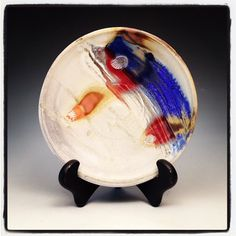 Justin Rothshank -- Wood fired porcelain plate with red and blue streaks