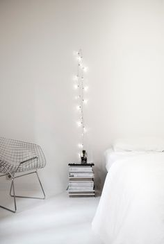 Bertoia diamond chair | white bed linen | stack of magazines | fairy lights