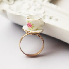 Adorable ring is made of a miniature ceramic teacup and saucer with a pink pattern on and a gold rim.