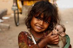 Little girl in India cuddles a baby monkey. Monkeys roam the streets and perch on buildings in parts of India, so they are a common sight there.
