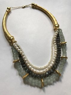 We love the rich, glowing aura of Laboradite and paired it here with elements that remind us of the sea: African recycled glass beads and precious freshwater pearls. The 24 kt vermeil gold* collar tubes are made by hand in Thailand. All gold elements in this piece are nickel-free vermeil. Necklace