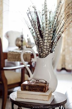 Striped pheasant feathers in a white stoneware pitcher make a handsome end-table vignette when paired with a stack of antique books.