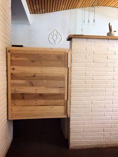 """Mobiliario en baño de """"señoras"""" sobre de lavamanos con tronco de madera de Wengue, pica confeccionada con olla (instalación de grifo), tapa de Wc con madera de Palet, espejo con luz con marco en madera de Palet, papelera con logo del Restaurante y estante/buzón sugerencia de los dueños para que su clientela siga dejando su huella, en el baño de """"señores"""" misma decoración y creamos la puerta vaivén de servicio a la cocina."""