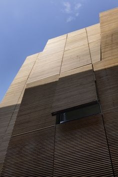 Perceived as a giant blind façade from an angle, the wooden surface can be seen as a tulle curtain that filters the light and works as an element that controls the sunlight .