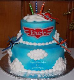 """6"""" & 10"""" cakes iced in buttercream then sprayed with blue spray. Logo/name was done in fondant. Toppers are toys. TFL!"""