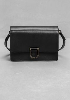 Large D-ring buckle closure defines this city-chic shoulder bag made from structured leather.
